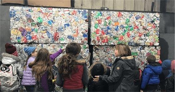 Students look at compressed garbage cubes at the dump