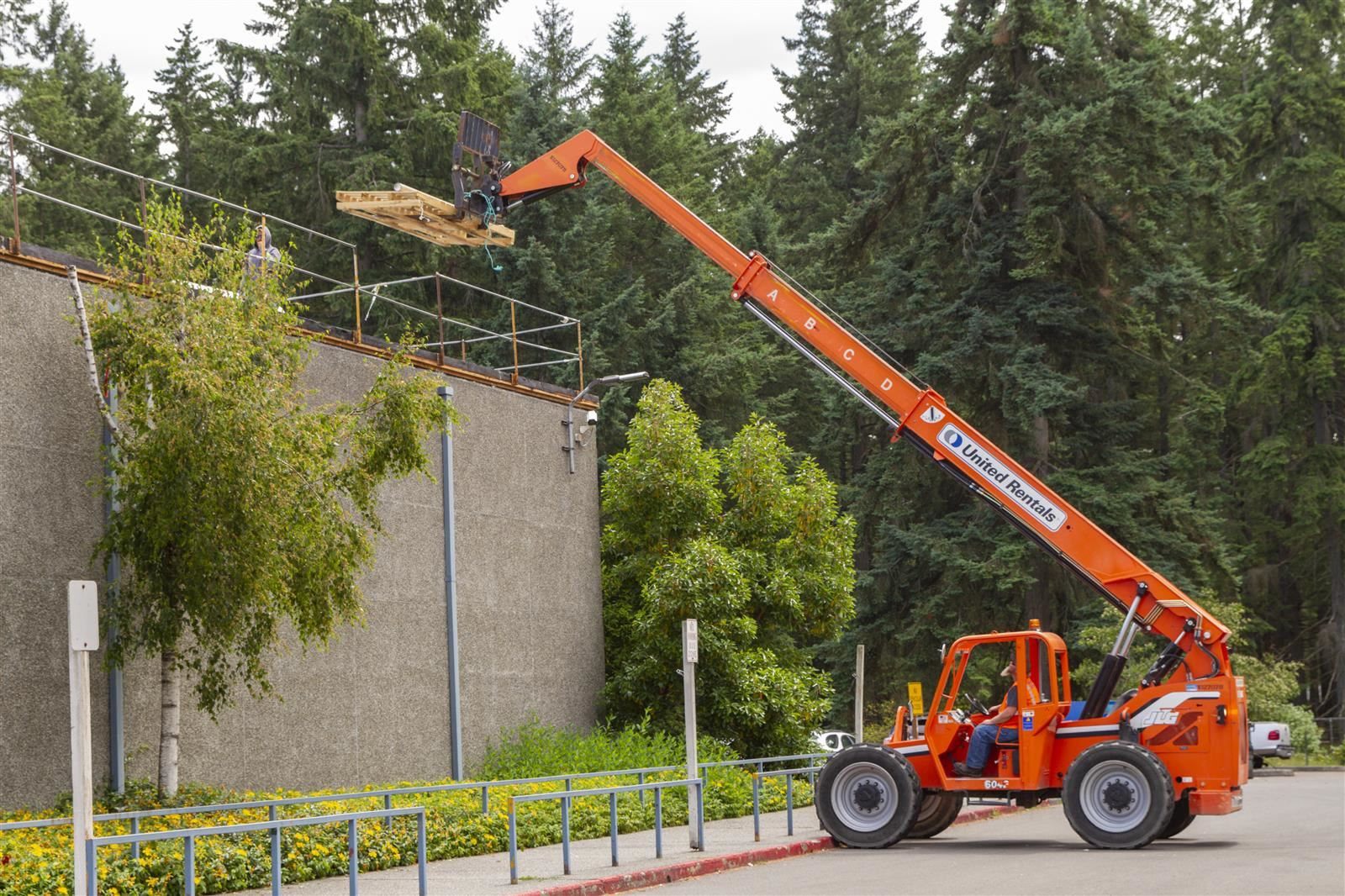 A crane lifts wood to the roof of Naches Trail Elementary