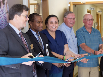 A group of people cut the ribbon on a new health care facility