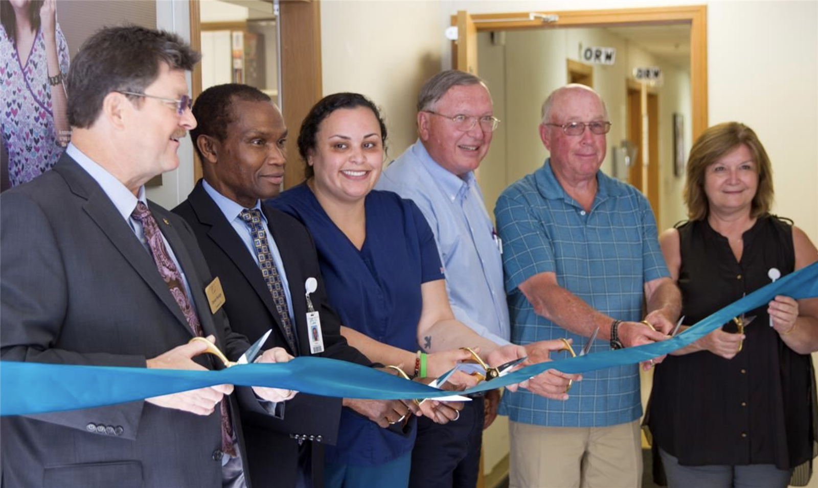 Six people cut a blue ribbon to open a new facility