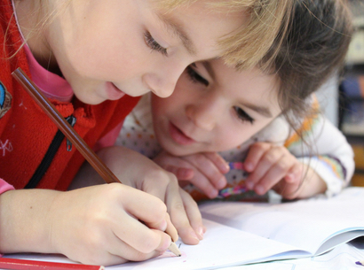Two children writing together with a pencil